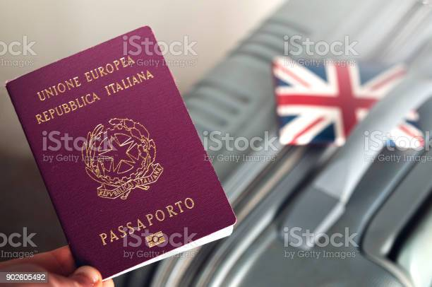 An italian passport holded over a suitcase with an english id holder picture id902605492?b=1&k=6&m=902605492&s=612x612&h=k5vjmhseezf7nvlxcmmekaq2qhlrymx abcltdmptf0=