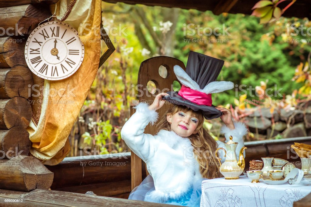 An little beautiful girl holding cylinder hat with ears like a rabbit over head at the table stock photo
