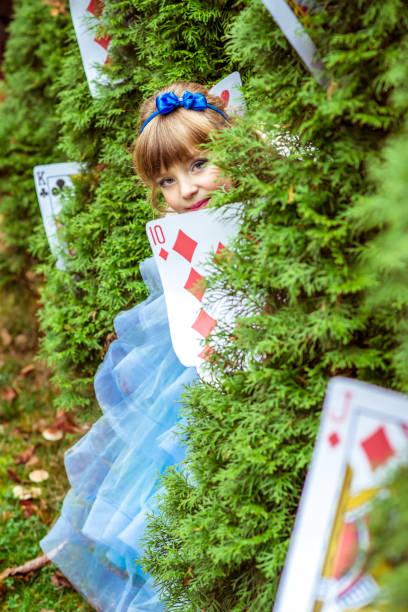 eine kleine schöne mädchen in einem langen blauen kleid suchen unter den tannen - natürliche make up kurse stock-fotos und bilder
