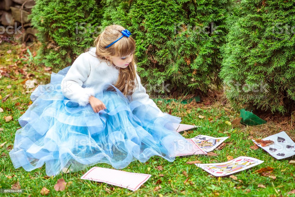An little beautiful girl in a long blue dress sitting on the grass and playing with large game cards stock photo