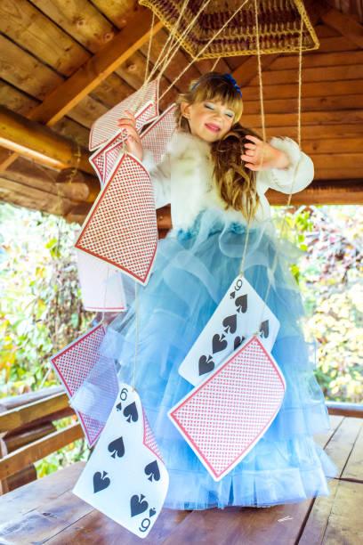 eine kleine schöne mädchen spielen und tanzen mit großen spielkarten auf dem tisch - natürliche make up kurse stock-fotos und bilder