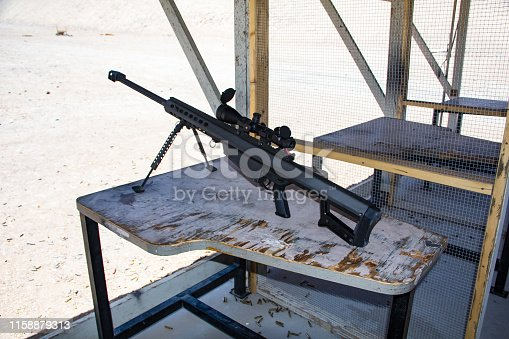 istock An mounted, unloaded, heavy  sniper riflea attached large scope for precision and accuracy, shooting .50 caliber cartridges with huge fire power on a shooting range 1158879313