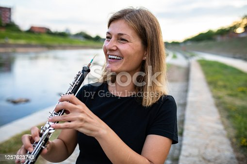 A blonde woman is holding the oboe close to her mouth and smiling on the riverbank