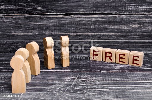 An ocher of wooden people in front of the inscription is for free. People are behind the discount and free goods. Low prices, sales, promotions and events. Black Friday, crazy crowd