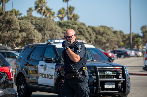 Ventura, California, United States -  August 7, 2020: An officer from the City of Ventura Police Department arrives to conduct a search of a suspect's vehicle at Ventura Harbor.  Two firearms were seized and two suspects arrested.  The incident happened at Ventura Harbor Cove Beach, in the parking lot.  The officer is putting a mask on due to Covid risk at the time.