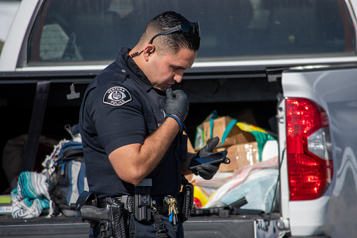 Ventura, California, United States -  August 7, 2020: An officer from the City of Ventura Police Department conduct a search of a suspect's vehicle at Ventura Harbor.  Two firearms were seized and two suspects arrested.  The incident happened at Ventura Harbor Cove Beach, in the parking lot.