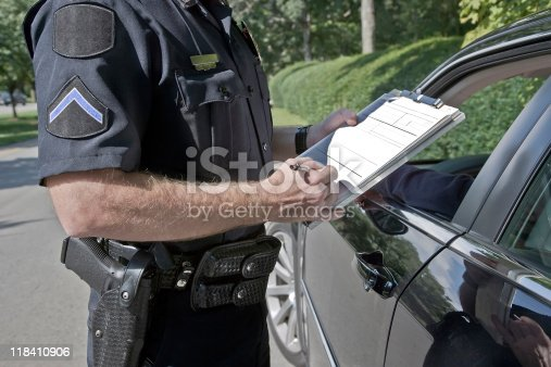 A police officer filling in a ticket by a pulled over car.