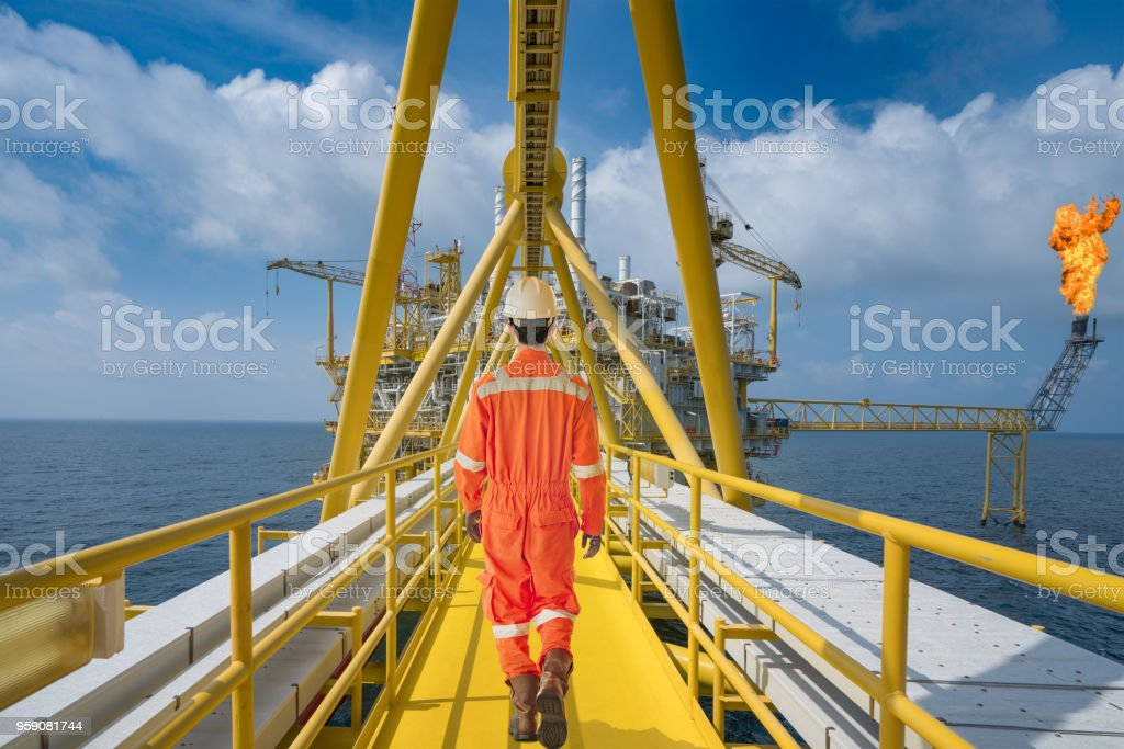 An Offshore Oil Rig Worker Walk To Oil And Gas Central Facility To Working  In Process Area Maintenance And Service Operation At Hazardous Area Stock