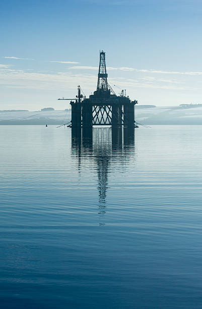 An oil rig in the middle of a body of water  stock photo