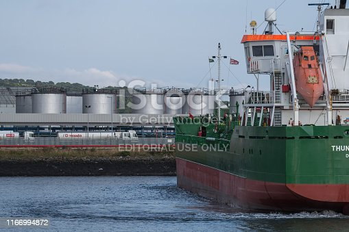 Belfast, Northern Ireland, UK - July 29, 2019: An inshore oil tanker docking to off-load its cargo at Belfast Harbour's fuel storage facility.   The ship, the Thun Gemini, was built in 2003 by FERUS SMIT SCHEEPSWERF - HOOGEZAND, NETHERLANDS.  It is registered in the Netherlands and operated by THUN SHIPMANAGEMENT - LIDKOPING, SWEDEN.   In the distance are the Holywood Hills (part of Belfast's green belt).