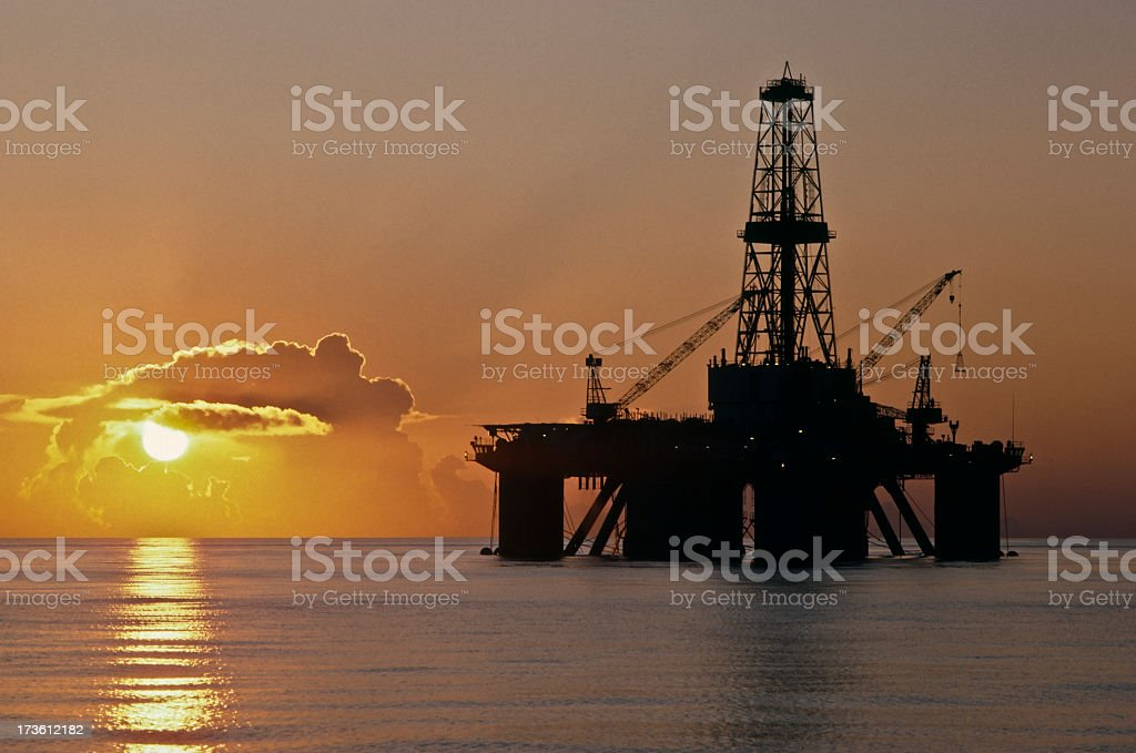 An oil well with cranes in the sea at dusk in Texas stock photo
