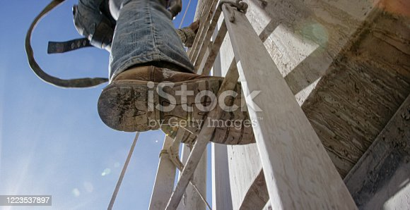 An Oilfield Worker Climbs a Ladder on the Side of a Mud Tank at an Oil and Gas Drilling Pad Site on a Sunny Morning