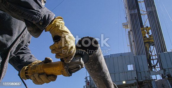 An Oilfield Worker Grinds a Metal Pipe Next to a Derrick at an Oil and Gas Drilling Pad Site on a Sunny Morning