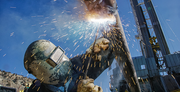 An Oilfield Worker Welds an End Cap to a Pipe as Sparks Fly Next to a Derrick at an Oil and Gas Drilling Pad Site on a Sunny Day