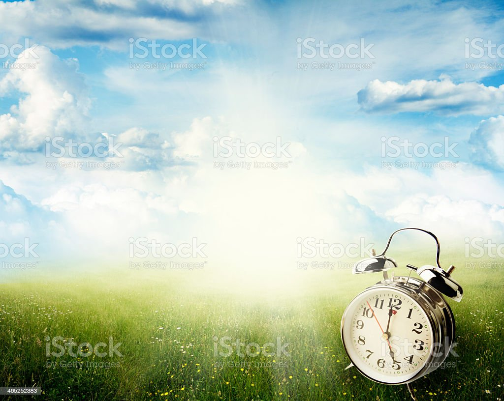 An old alarm clock on a springtime background stock photo