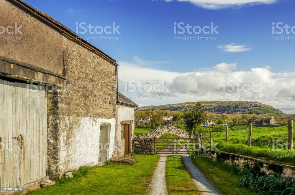 An old barn in Cumbria on a sunny day with a wooden gate and distant hills - Photo