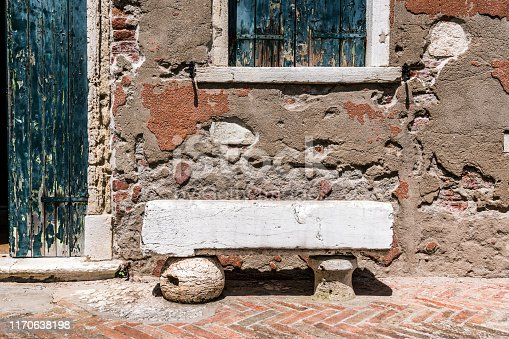 Ancient bench of a large piece of marble at the wall of a medieval Italian house on the island of Torcello.