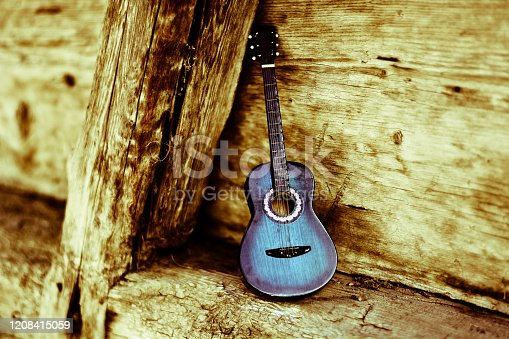 istock an old Blues guitar leaning against wood 1208415059