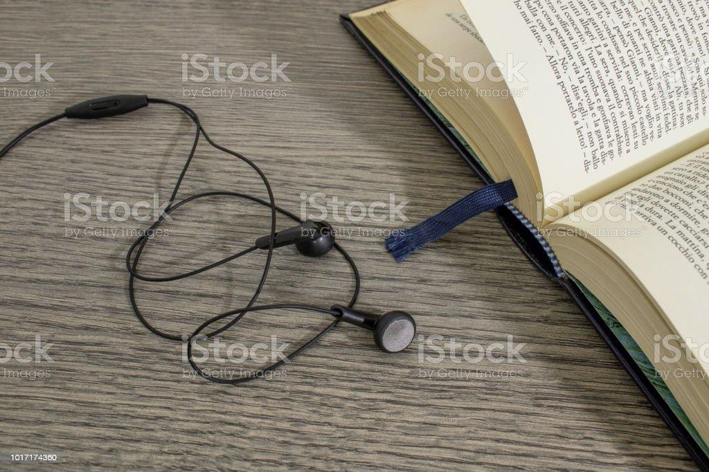 Um livro velho e fones de ouvido em uma composição de mesa de madeira - foto de acervo