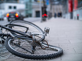 istock An old broken and bent bicycle with a rusted chain discarded in the street 1097968876