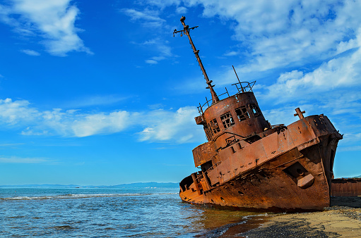 shipwreck or wrecked cargo ship abandoned on sea bay