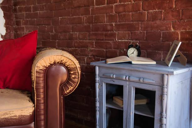 Un viejo sillón marrón y un reloj con un libro en un buffet de madera - foto de stock