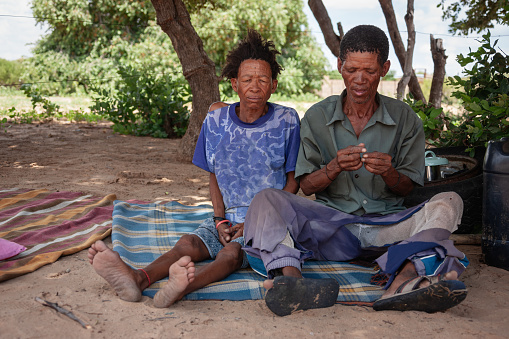 an old bushman man from Central Kalahari, village New Xade in Botswana, in front of his yard sitting with the wife