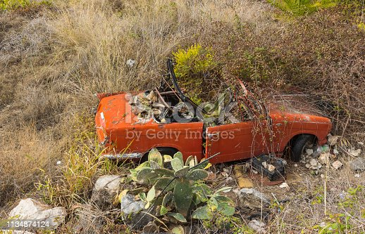 Old car wreck standing beside a road down the hill in andalusia. Car is a wrecked oldtimer cabriolet which surely was a nice automobile in former times. Plants begin to overgrow and hide it completely