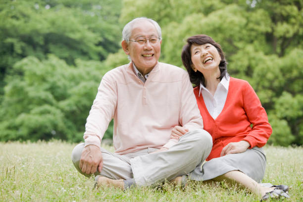 An old couple sitting on the grass in the Park, to have a conversation stock photo