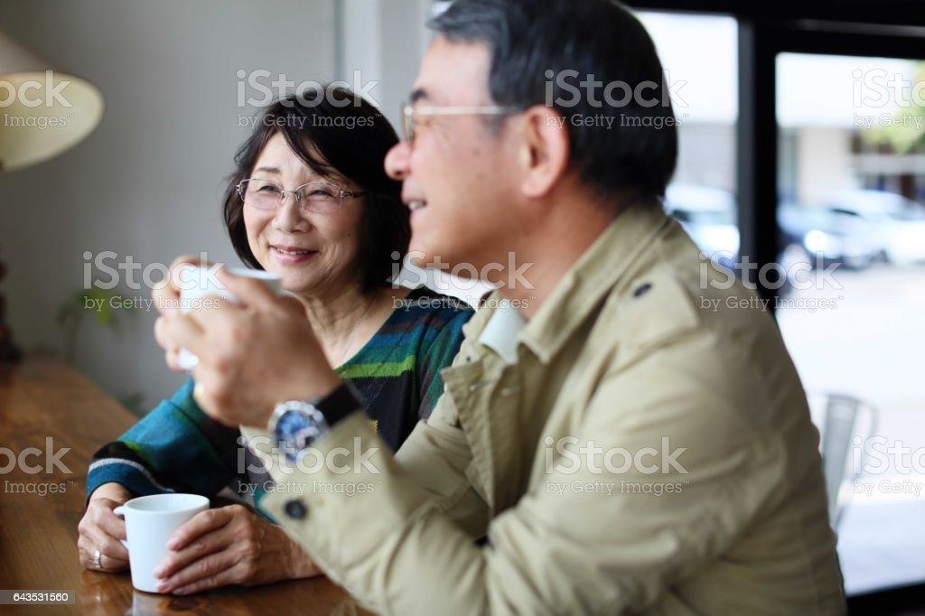 An old couple talking happily in a cafe stock photo