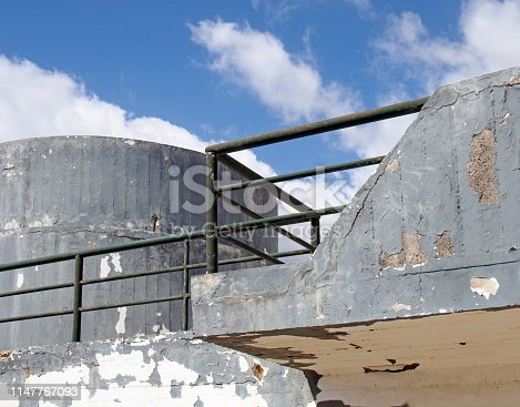 an old crumbling concrete military bunker type structure with rounded windowless surfaces and a green railing against a blue cloudy sky