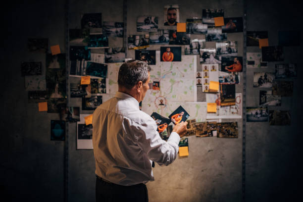 An old detective is looking at photos of suspects in his office An old detective is looking at photos of suspects in his office detective stock pictures, royalty-free photos & images