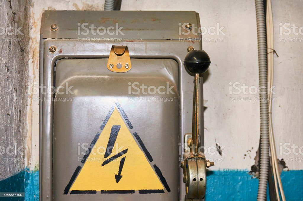An old electric high-voltage switch with a painted danger sign. royalty-free stock photo