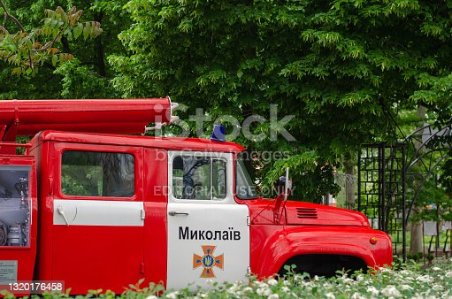 istock An old fire engine in an open-air museum. White and red car on the background of green trees. 1320176458