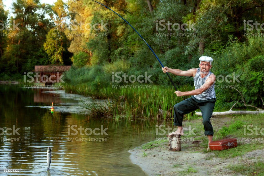 An old fisherman caught a fish in the lake. stock photo
