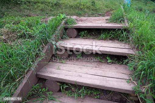 Summer. An old, home-made staircase made of planks and logs in the countryside.