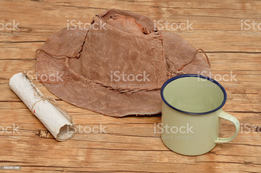 An old leather hat with a paper scroll and tin mug stock photo