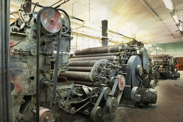 Una vieja máquina en una fábrica textil abandonada bajo el sol de la mañana - foto de stock