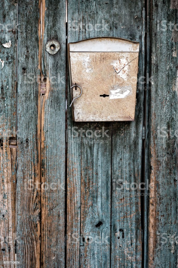 An old mailbox on green painted wooden door. royalty-free stock photo