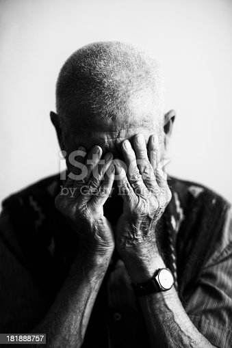 istock An old man covering his face with his hands in grief  181888757
