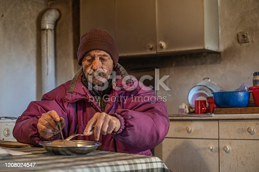 A senior man wearing a hat and a purple jacket eating in his kitchen stock photo