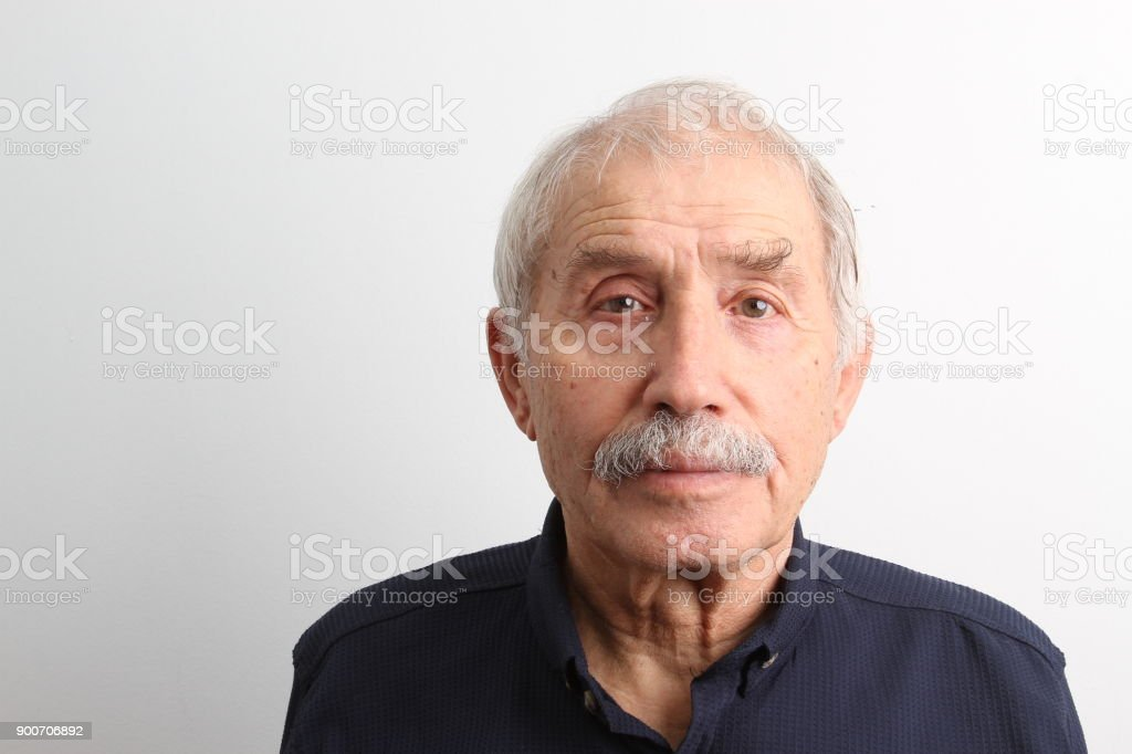 An old man looking at camera with a serious facial expression An old man looking at camera with a serious facial expression on white background 70-79 Years Stock Photo