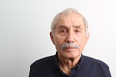 An old man looking at camera with a serious facial expression