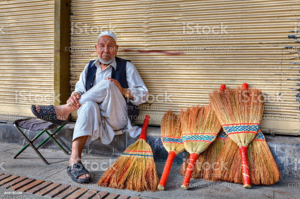 An old man sells brooms on a city street. stock photo