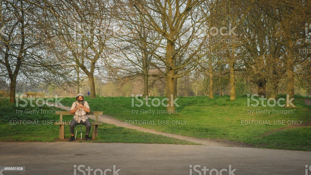 An Old Man Sitting On A Bench In A Park In London Stock Photo More