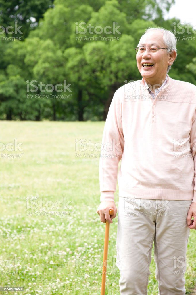 An old man with a cane to walk in the Park stock photo