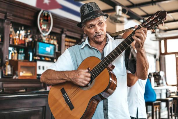 en gammal man med hatt spelar en akustisk gitarr i en bar i havanna, kuba. - celebrities of age bildbanksfoton och bilder