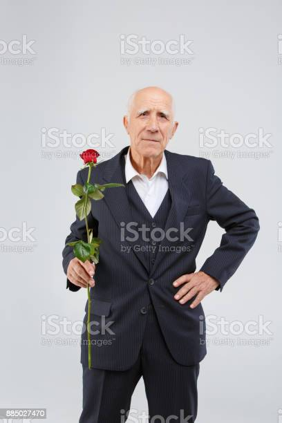 An old mature man in one hand holds red rose and the second hand on picture id885027470?b=1&k=6&m=885027470&s=612x612&h=j4we6iangfnal18xpe d7n1chsfa1qvge4zcbsbgdxc=