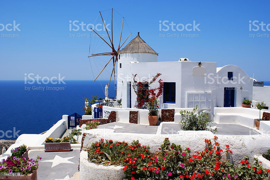 An old mill by a cliff on an all-white structure royalty-free stock photo