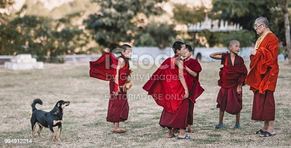 an old monk talking to a few young monk while a dog pass by outside the field of a Buddhism temple, Pari, Bhutan on 6th november 2017 during a break in the evening